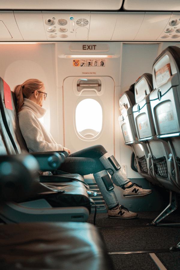 kvinde sidder i fly med yourboots travel